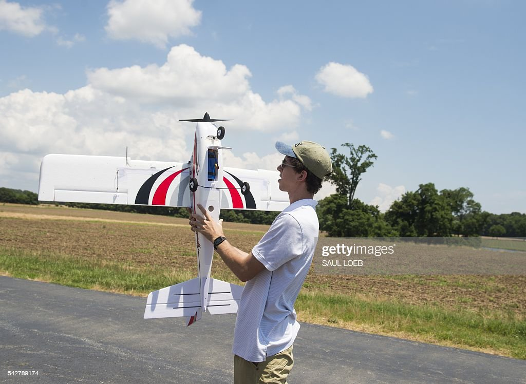 Joshua Gaus, a mechanical engineering student at the University of Maryland, holds a remote-controlled airplane that he has outfitted with autonomous flying controls so that it can fly itself prior to a flight at a testing site for the University of Maryland's Unmanned Aircraft Systems (UAS) programs in Bushwood, Maryland, June 24, 2016. The Federal Aviation Administration has unveiled new rules that clear the way for small, commercial drones to operate across US airspace. Drone operators will be allowed to fly commercial craft weighing less than 55 pounds (25 kilograms) during daylight hours, provided they can maintain a clear view of the drone at all times. / AFP / SAUL
