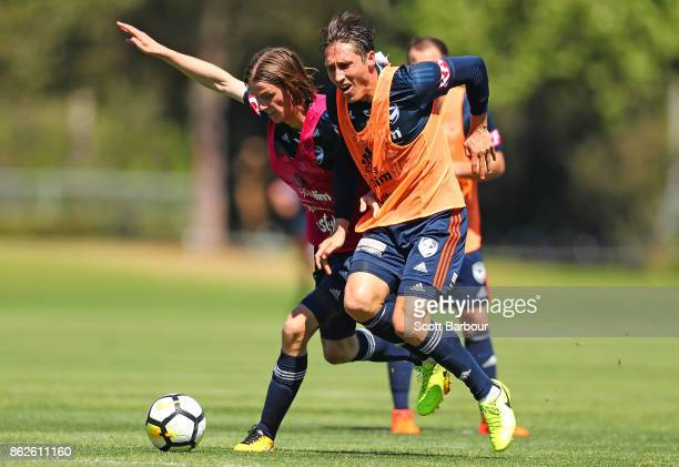 Joshua Hope and Mark Milligan of the Victory compete for the ball during a Melbourne Victory ALeague training session at Gosch's Paddock on October...