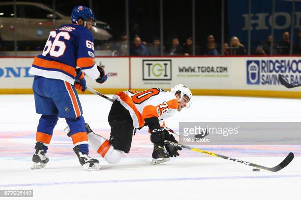 Joshua HoSang of the New York Islanders takes down Danick Martel of the Philadelphia Flyers in the neutral zone during the first period of a game at...