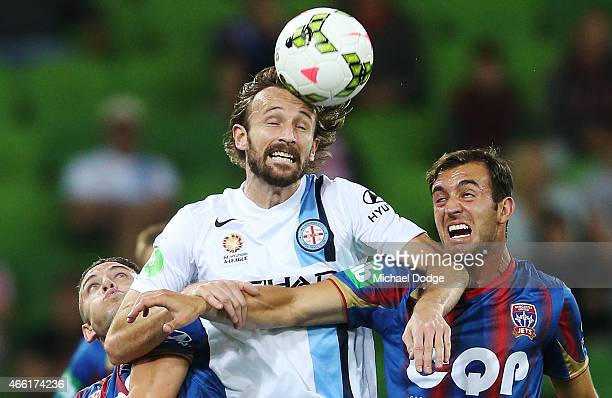 Joshua Kennedy of Melbourne City heads the ball away from Scott Neville of the Jets and Ben Kantarovski during the round 21 ALeague match between...