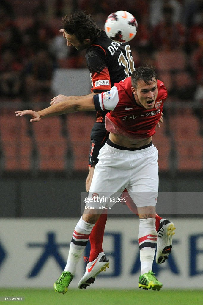 Joshua Kennedy #16 of Nagoya Grampus (L) and <a gi-track='captionPersonalityLinkClicked' href=/galleries/search?phrase=Aaron+Ramsey+-+Soccer+Player&family=editorial&specificpeople=4784114 ng-click='$event.stopPropagation()'>Aaron Ramsey</a> #16 of Arsenal compete for the ball during the pre-season friendly match between Nagoya Grampus and Arsenal at Toyota Stadium on July 22, 2013 in Toyota, Aichi, Japan.