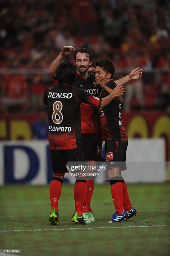 Joshua Kennedy (C) of Nagoya Grampus celebrates scoring his team's second goal with his team mates Jungo Fujimoto (L) and Hayuma Tanaka (R) during the J.League match between Nagoya Grampus and Urawa Red Diamonds at Toyota Stadium on August 10, 2013 in Toyota, Aichi, Japan.