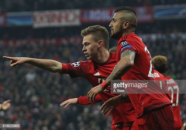 Joshua Kimmich and Arturo Vidal of Bayern Muenchen celebrate their team's thrid goal during the Champions League round of 16 second leg match between...