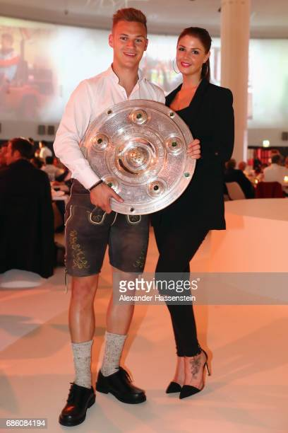 Joshua Kimmich and his partner Lina Meyer pose with the trophy during the FC Bayern Muenchen Championship party following the Bundesliga match...