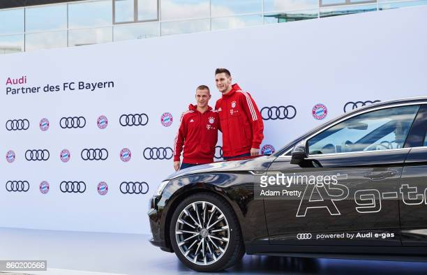 Joshua Kimmich and Niklas Suele of FC Bayern Muenchen pose with their car during the FC Bayern Muenchen New Car Handover at the Audi Forum on October...
