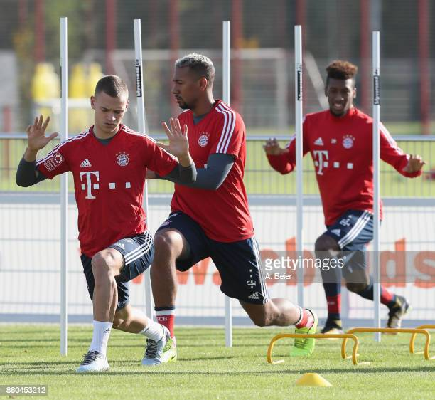 Joshua Kimmich Jerome Boateng and Kingsley Coman of FC Bayern Muenchen warm up during a training session at the Saebener Strasse training ground on...