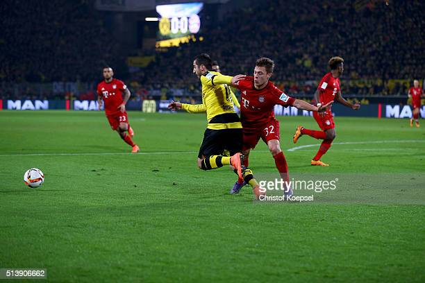 Joshua Kimmich of Bayern challenges Henrikh Mkhitaryan of Dortmund during the Bundesliga match between Borussia Dortmund and FC Bayern Muenchen at...