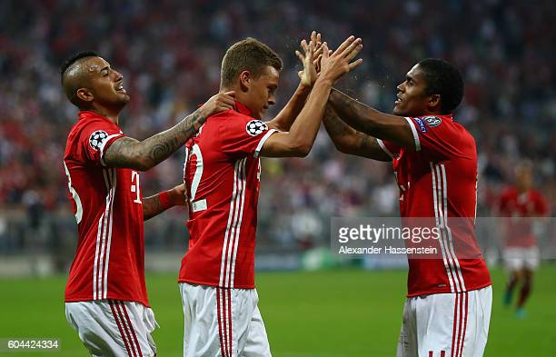 Joshua Kimmich of Bayern Muenchen celebrates scoring his sides third goal wih team mates Douglas Costa and Arturo Vidal during the UEFA Champions...