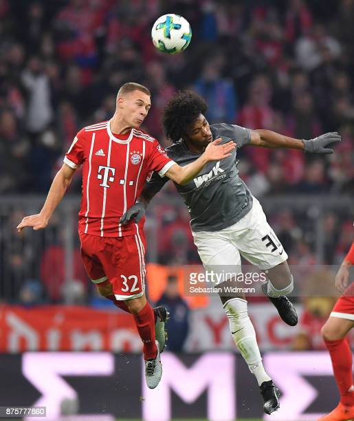 Joshua Kimmich of Bayern Muenchen fights for the ball with Caiuby of Augsburg during the Bundesliga match between FC Bayern Muenchen and FC Augsburg...