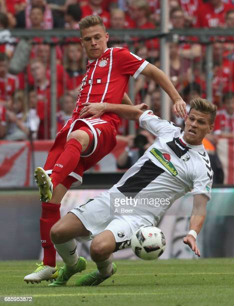 Joshua Kimmich of Bayern Muenchen fights for the ball with Florian Niederlechner of Freiburg the Bundesliga match between Bayern Muenchen and SC...