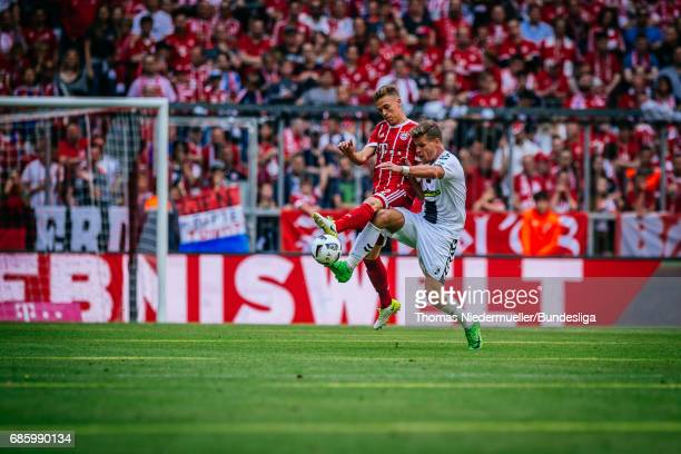 Joshua Kimmich of Bayern Muenchen fights for the ball with Florian Niederlechner of Freiburg during the Bundesliga match between Bayern Muenchen and...