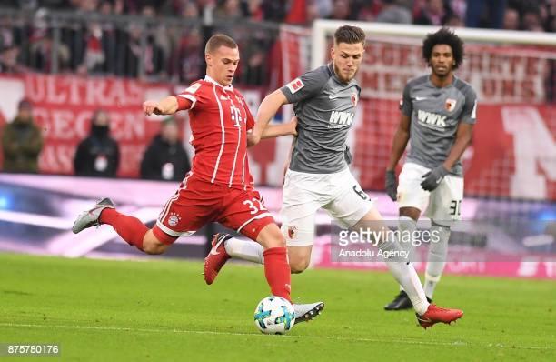 Joshua Kimmich of Bayern Munich in action against Jeffrey Gregoritsch of Augsburg during the Bundesliga soccer match between FC Bayern Munich and FC...