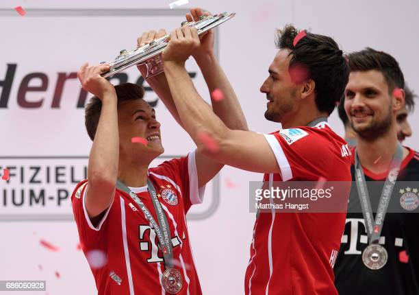 Joshua Kimmich of FC Bayern Muenchen and Mats Hummels of FC Bayern Muenchen lift the Championship trophy in celebration of the 67th German...