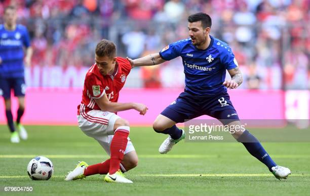 Joshua Kimmich of FC Bayern Muenchen challenges Jerome Gondorf of SV Darmstadt during the Bundesliga match between Bayern Muenchen and SV Darmstadt...