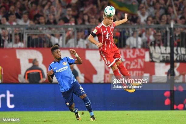 Joshua Kimmich of FC Bayern Muenchen goes for a header as Leon Bailey of Bayer Leverkusen watches during the Bundesliga match between FC Bayern...