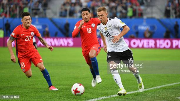 Joshua Kimmich of Germany attempts to take the ball away from Charles Aranguiz of Chile and Gonzalo Jara of Chile during the FIFA Confederations Cup...