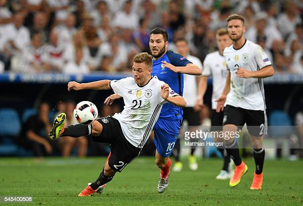 Joshua Kimmich of Germany controls the ball under pressure from AndrePierre Gignac of France during the UEFA EURO semi final match between Germany...
