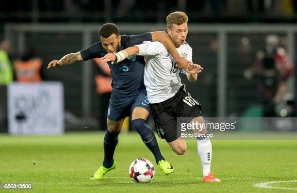 Joshua Kimmich of Germany is challenged by Ryan Bertrand of England during the international friendly match between Germany and England at Signal...