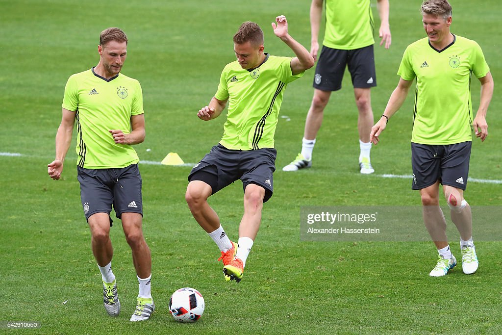 Joshua Kimmich (C) of Germany plays the ball with his team mates Benedikt Hoewedes (L) and Bastian Schweinsteiger (R) during a Germany training session ahead of their Euro 2016 round of 16 match against Slovakia at Ermitage Evian on June 25, 2016 in Evian-les-Bains, France.