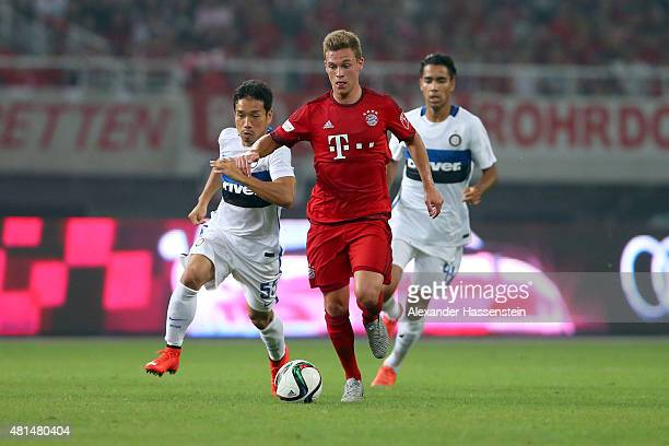 Joshua Kimmich of Muenchen battles for the ball with Yuto Nagatomo of Milan and his team mate Pedro Delgado during the international friendly match...