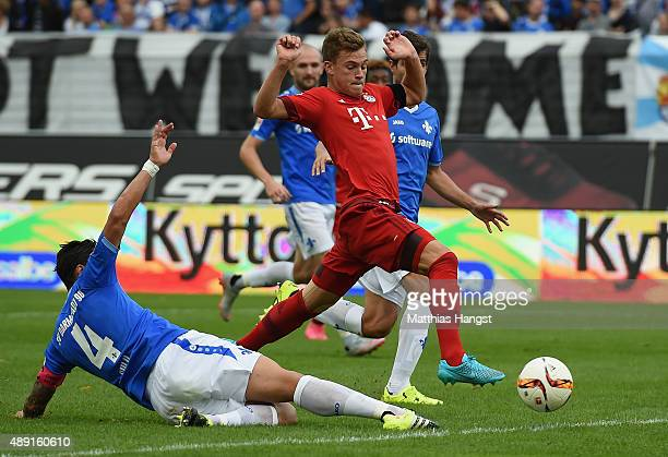 Joshua Kimmich of Muenchen is challenged by Aytac Sulu of Darmstadt during the Bundesliga match between SV Darmstadt 98 and FC Bayern Muenchen at...