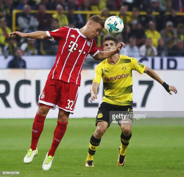 Joshua Kimmich of Muenchen is challenged by Christian Pulisic of Dortmund during the DFL Supercup 2017 match between Borussia Dortmund and Bayern...