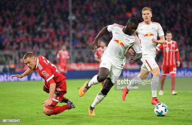Joshua Kimmich of Muenchen is challenged by Dayot Upamecano of Leipzig during the Bundesliga match between FC Bayern Muenchen and RB Leipzig at...