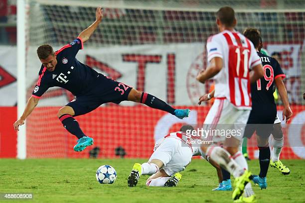Joshua Kimmich of Muenchen is challenged by Kostas Fortounis of Olympiacos during the UEFA Champions League Group F match between Olympiacos FC and...