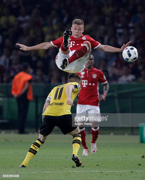 Joshua Kimmich of Muenchen is challenged by Marco Reus of Dortmund during the DFB Cup Final 2016 between Bayern Muenchen and Borussia Dortmund at...