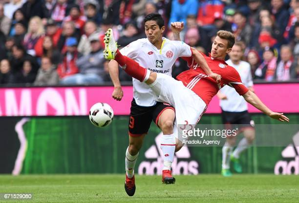 Joshua Kimmich of Munich and Yoshinori Muto of Mainz vie for the ball during the Bundesliga soccer match between FC Bayern Munich and Mainz 05 at the...