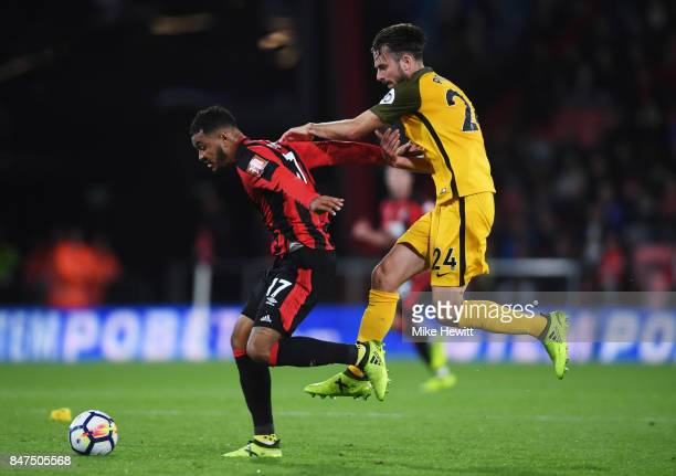 Joshua King of AFC Bournemouth fends off Davy Propper of Brighton and Hove Albion during the Premier League match between AFC Bournemouth and...