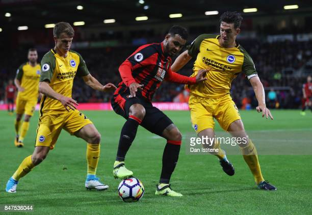 Joshua King of AFC Bournemouth is marshalled by Solly March and Lewis Dunk of Brighton and Hove Albion during the Premier League match between AFC...