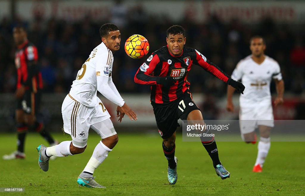 Joshua King of Bournemouth and Kyle Naughton of Swansea City compete for the ball during the Barclays Premier League match between Swansea City and...