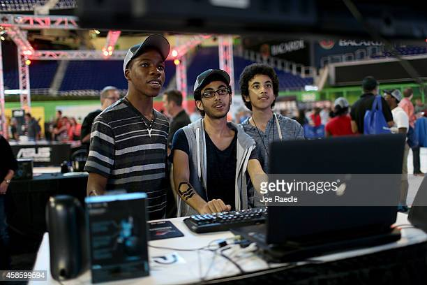 Joshua Legis Moshe Tzafrir and Abir Tzafrir check out the items on display at the Logitech booth as they play a Doom 3 videogame during the...