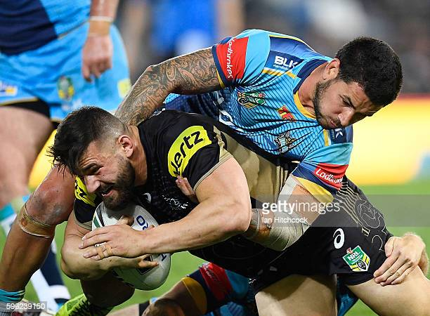 Joshua Mansour of the Panthers is tackled by Nathan Peats of the Titans during the round 25 NRL match between the Gold Coast Titans and the Penrith...