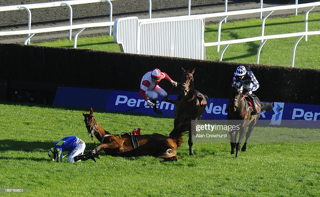 Joshua Moore riding Via Sundown fall at the last and force Charlie Poste to be unseated from his mount Badgers Cove at Kempton Park racecourse on November 04, 2013 in Sunbury, England.