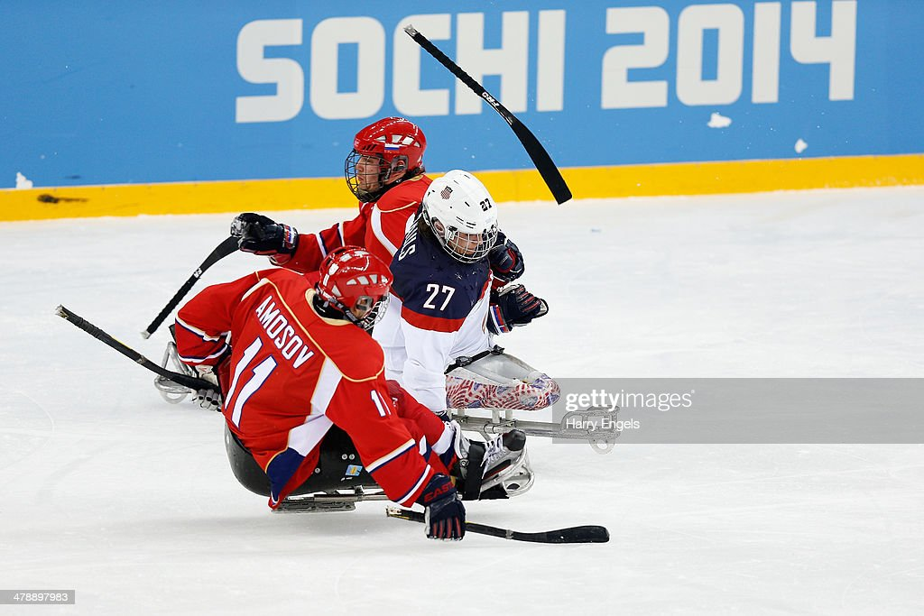 Joshua Pauls of USA is tackled by Alexey Amosov of Russia (L) as a hockey stick goes flying during the Ice Sledge Hockey Gold Medal match between Russia and USA at the Shayba Arena during day eight of the 2014 Paralympic Winter Games on March 15, 2014 in Sochi, Russia.