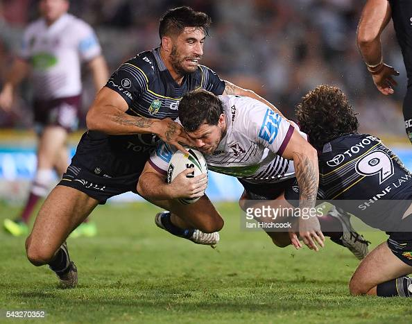 Joshua Starling of the Sea Eagles is tackled by James Tamou and Jake Granville of the Cowboys during the round 16 NRL match between the North...