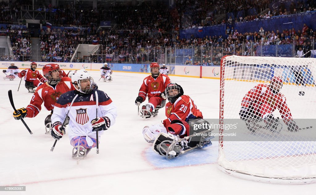 Joshua Sweeney of the United States scores past Vladimir Kamantcev of Russia during the Ice Sledge Hockey Gold Medal game between the United States and Russia on day eight of the Sochi 2014 Paralympic Winter Games at Shayba Arena on March 15, 2014 in Sochi, Russia.