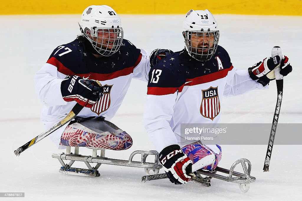 Joshua Sweeney of the USA celebrates with Joshua Pauls of the USA after scoring a goal during the ice sledge hockey gold medal game between the Russian Federation and the United States of America at the Shayba Arena during day eight of the 2014 Paralympic Winter Games on March 15, 2014 in Sochi, Russia.