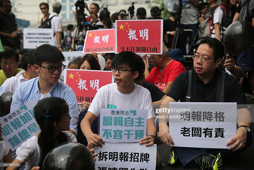 Joshua Wong (C), a student activist, holds a sign with people gathered outside the offices of Ming Pao during a rally organised by Journalist groups to protest the sacking of Ming Pao's Executive Chief Editor Keung Kwok-yuen in Hong Kong on May 2, 2016. / AFP / ISAAC
