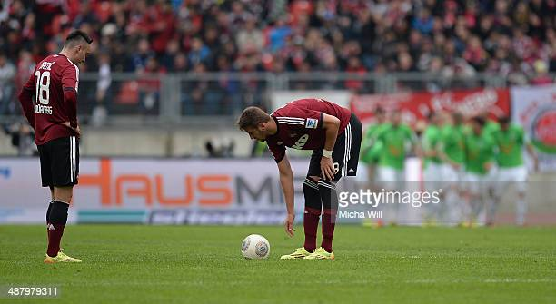 Josip Drmic and Tomas Pekhart of Nernberg look on while Hannover celebrates their second goal during the Bundesliga match between 1 FC Nuernberg and...