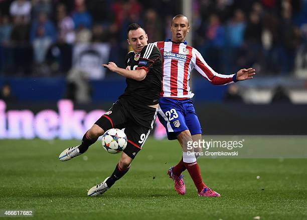 Josip Drmic of Bayer Leverkusen and Miranda of Atletico Madrid compete for the ball during the UEFA Champions League round of 16 match between Club...