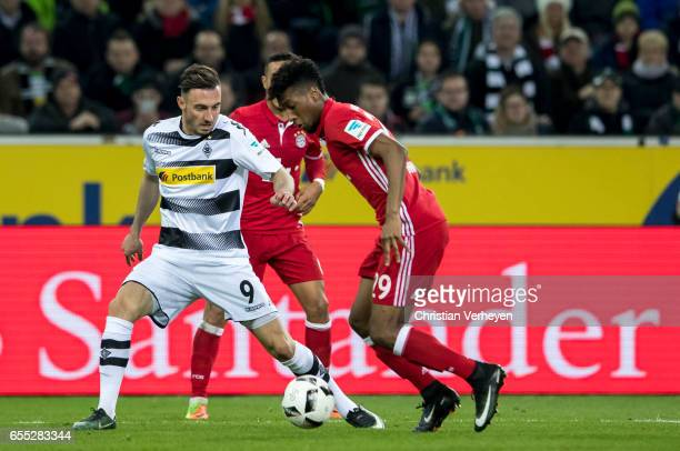 Josip Drmic of Borussia Moenchengladbach and Kingsley Coman of FC Bayern Muenchen battle for the ball during the Bundesliga Match between Borussia...