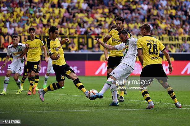 Josip Drmic of Borussia Moenchengladbach misses a chance at goal as he takes a shot under the pressure of Henrikh Mkhitaryan of Borussia Dortmund...