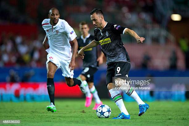 Josip Drmic of Borussia Monchengladbach competes for the ball with Steven NZonzi of Sevilla FC during the UEFA Champions League Group D match between...