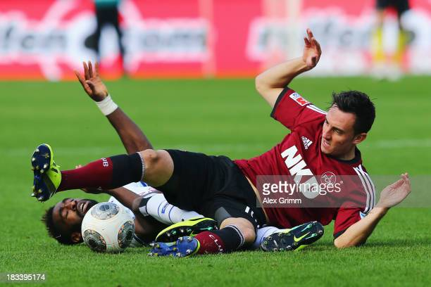 Josip Drmic of Nuernberg is challenged by Johan Djourou of Hamburg during the Bundesliga match between 1 FC Nuernberg and Hamburger SV at Grundig...
