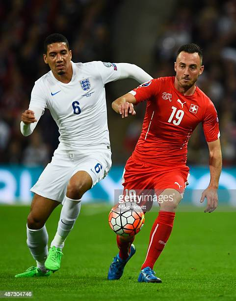 Josip Drmic of Switzerland and Chris Smalling of England watch the ball during the UEFA EURO 2016 Group E qualifying match between England and...