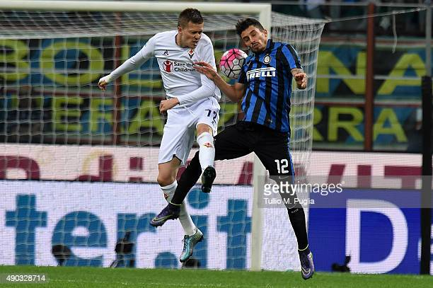 Josip Ilicic of Fiorentina and Alex Telles of Internazionale Milano jump for a header during the Serie A match between FC Internazionale Milano and...