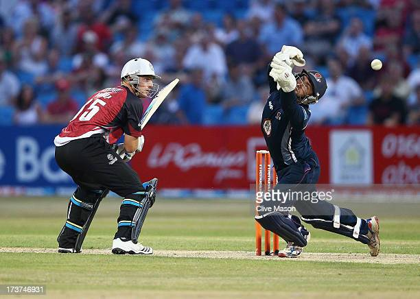 Joss Buttler of Somerset plays a shot as David Murphy of Northants attempts to stop it during the Friends Life T20 match between Northampton...